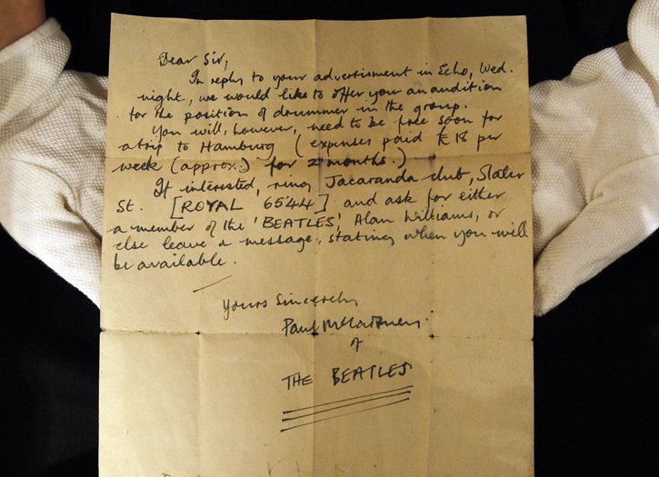 A Christie's employee displays a letter inviting an unknown drummer to audition for The Beatles.