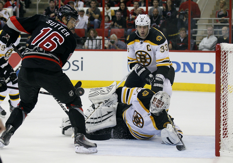 Bruins goalie Tim Thomas falls to the ice to stop Carolina's Brandon Sutter in tonight's game at Raleigh, N.C. The Bruins were beaten, 3-2.