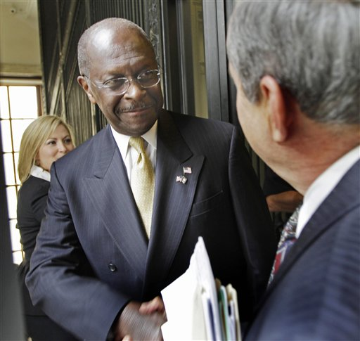 Herman Cain is greeted by lawmakers at the statehouse in Concord, N.H., on Wednesday.