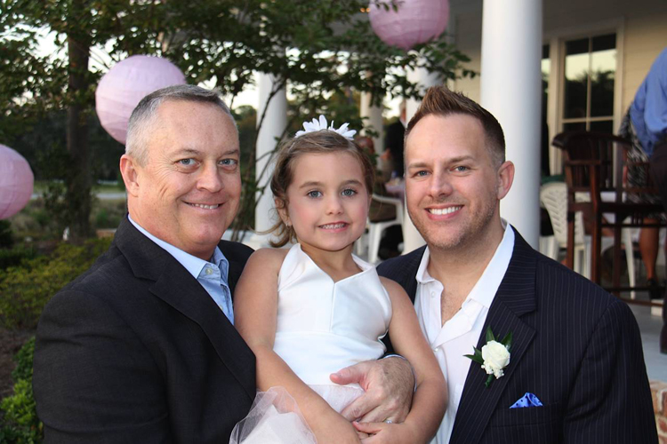 Jeff Littlefield, left, and his husband Tommy Starling pose with their 5-year-old daughter, Carrigan Starling-Littlefield, at a friend's wedding in Pawley's Island, S.C.