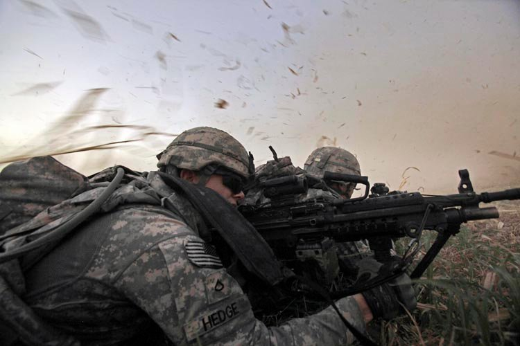 In this Aug. 8, 2011, photo, U.S. Army Pvt. 1st Class David Hedge from Bealeton, Va., front, and fellow soldiers from 1st Battalion, 18th Infantry Regiment, are bathed in rotor wash moments after arriving by Blackhawk helicopter for an operation to disrupt weapons smuggling in Istaqlal, north of Baghdad. President Barack Obama says all U.S. combat troops will come home from Iraq by the end of the year.