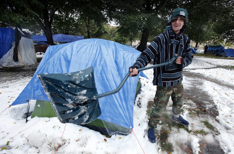 Blake Smith shovels snow in front of a tent at an Occupy Maine camp in Portland's Lincoln Park today.