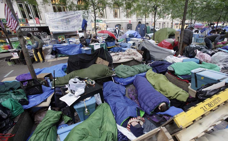"""Occupy Wall Street protesters sleep in New York's Zuccotti Park on Sunday. With thousands of people roughing it in parks for up to six weeks related to the """"Occupy"""" demonstrations, public health is a growing worry in the encampments."""