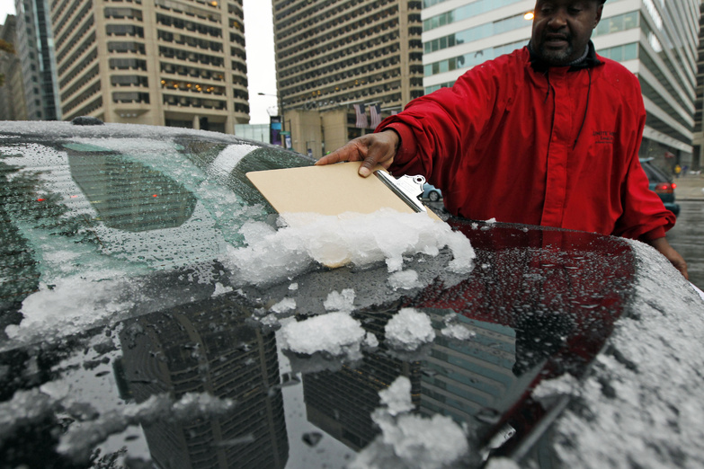 A man uses a clipboard to scrape the snow off of the back of his car window today in Philadelphia. A classic nor'easter was chugging along up the East Coast and expected to dump anywhere from a dusting of snow to about 10 inches throughout the region starting today, a decidedly unseasonal date for a type of storm more associated with midwinter.