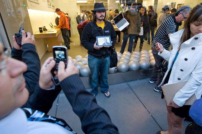 Steve Streza holds an iPad with a picture of Steve Jobs, as he and others gather outside an Apple store in San Francisco to mourn the Apple co-founder's death.