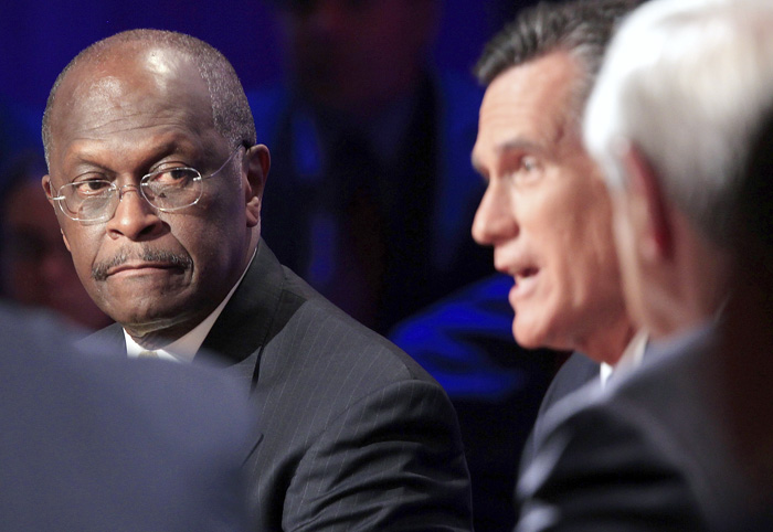 Republican presidential candidate businessman Herman Cain, and Rep. Ron Paul, R-Texas, right, listen as former Massachusetts Gov. Mitt Romney speaks during the Republican presidential debate at Dartmouth College in Hanover, N.H., on Tuesday.