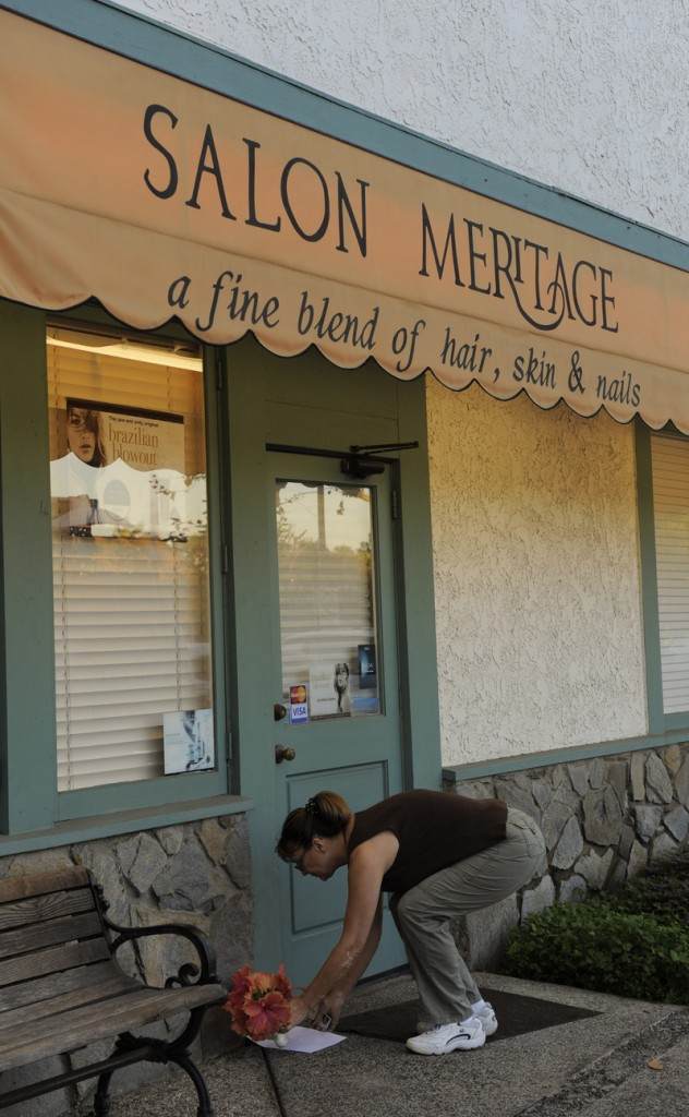 A woman places flowers Thursday in front of the salon in Seal Beach, Calif., where eight people were shot and killed Wednesday. Police arrested Scott Dekraai about a half-mile from the scene.