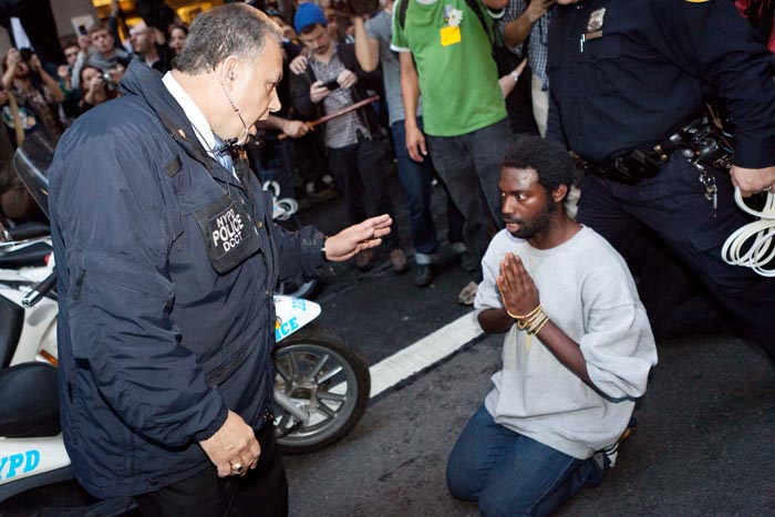 A police officer warns a protester of impending arrest if he does not move from the path of police scooters, as hundreds of Occupy Wall Street protesters march on the financial district after being heartened by a postponement of a scheduled cleanup of their camp at Zuccotti Park today.