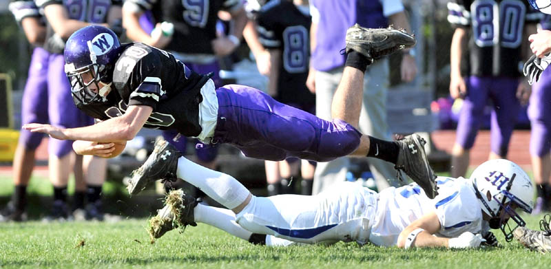 Staff photo by Michael G. Seamans Waterville high School running back Evan Greatorex, 30, dives for extra yardage over Madison high School defender Cody Soucier, 3, in the second quarter at Waterville Senior High School Saturday. Waterville defeated Madison 55-36.