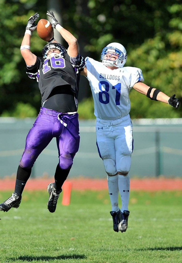 Staff photo by Michael G. Seamans Waterville High School's Aaron Saucier, 16, left, intercepts a pass intended for Madison High School receiver Matt Soucy, 81, in the second quarter at Waterville Senior High School Saturday. Waterville defeated Madison 55-36.
