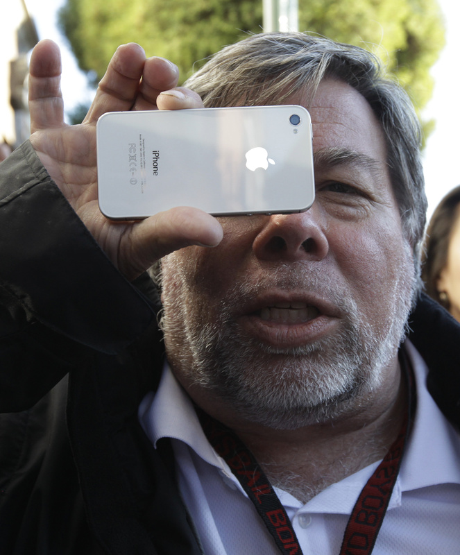 Apple co-founder Steve Wozniak holds up his new Apple iPhone 4S at the Apple store in Los Gatos, Calif., on Friday. He was first in line at the Los Gatos Apple store after arriving Thursday afternoon.
