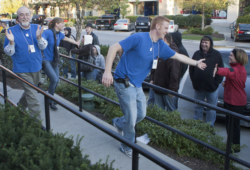 Apple store employees greet people waiting in line to buy the new iPhone 4S in Omaha, Neb., on Friday.