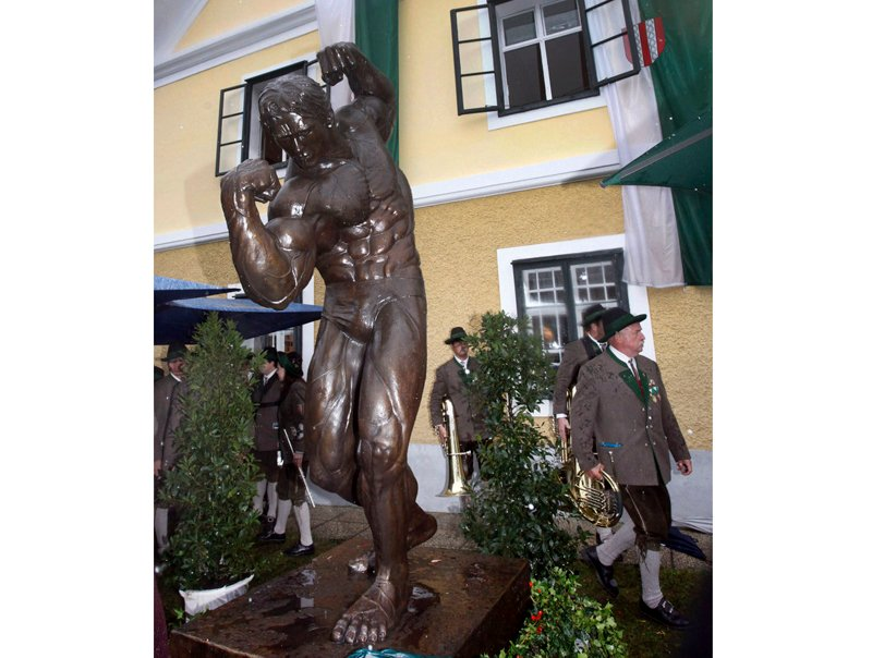 Austrians in traditional clothes pass a sculpture of former California Gov. Arnold Schwarzenegger during the inauguration of a museum in the house of Schwarzenegger's birth in Thal, Austria, on Friday.
