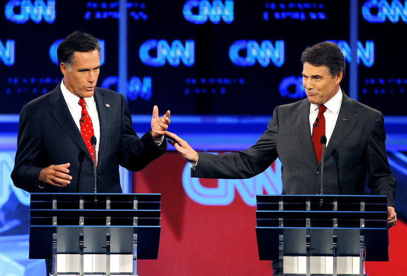 Former Massachusetts Gov. Mitt Romney, left, and Texas Gov. Rick Perry gesture during a Republican debate last month in Tampa, Fla. Neither frontrunner has yet to catch fire with the GOP base.