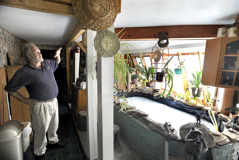 Mayhew stands in a greenhouse he attached to his house to bring sunlight and heat into the kitchen. The brick-lined pool of water stores warmth and moderates temperature swings.