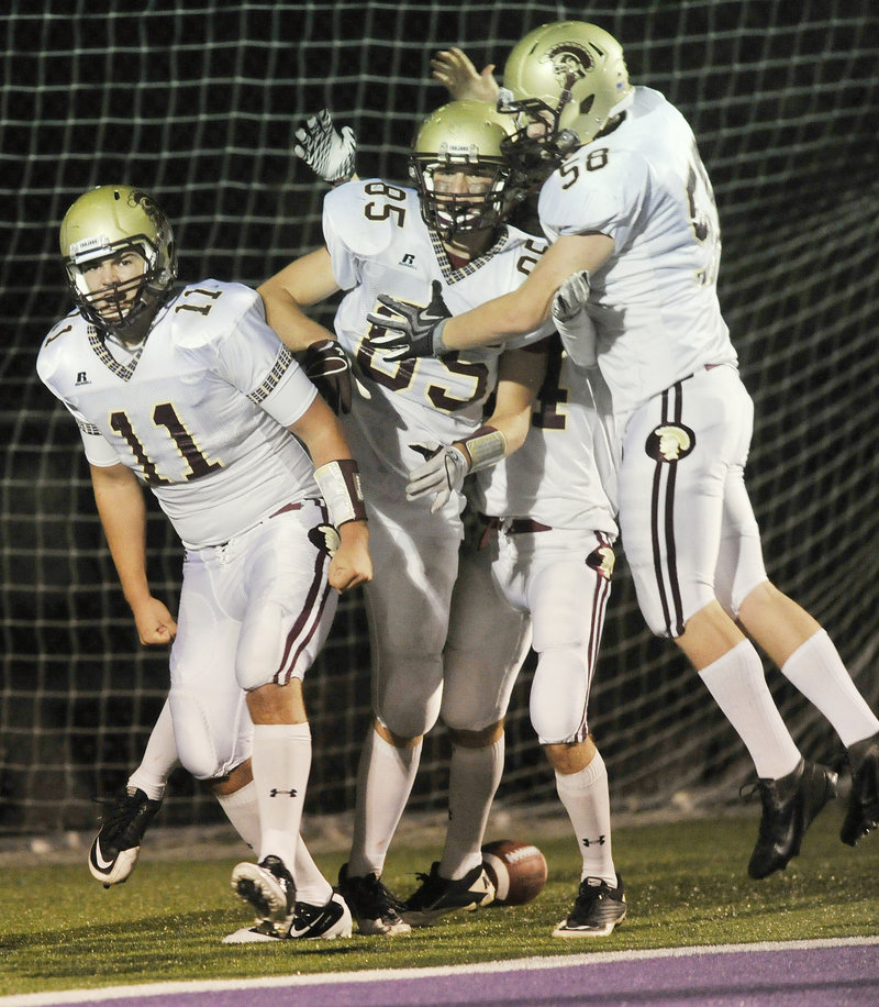 Thornton Academy quarterback Eric Christensen, left, is joined by teammates after scoring on an 8-yard run in the final minute of the first half Friday night. The Trojans went on to beat Deering.
