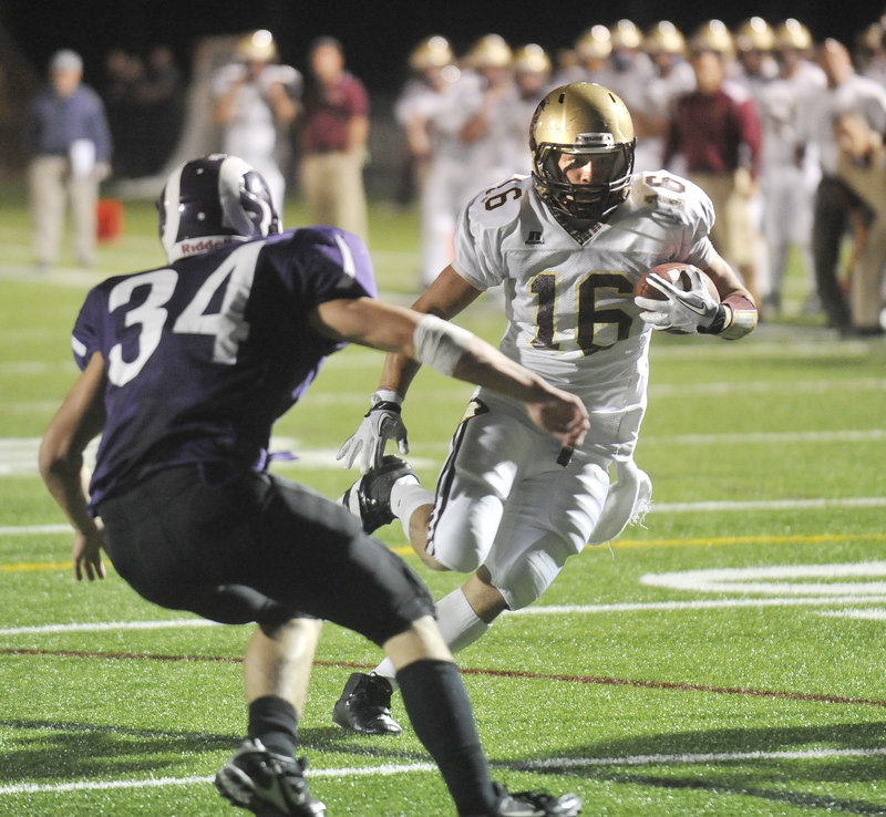Andrew Libby of Thornton Academy keeps his eyes on the end zone while searching for a way to elude Kenny Sweet of Deering.