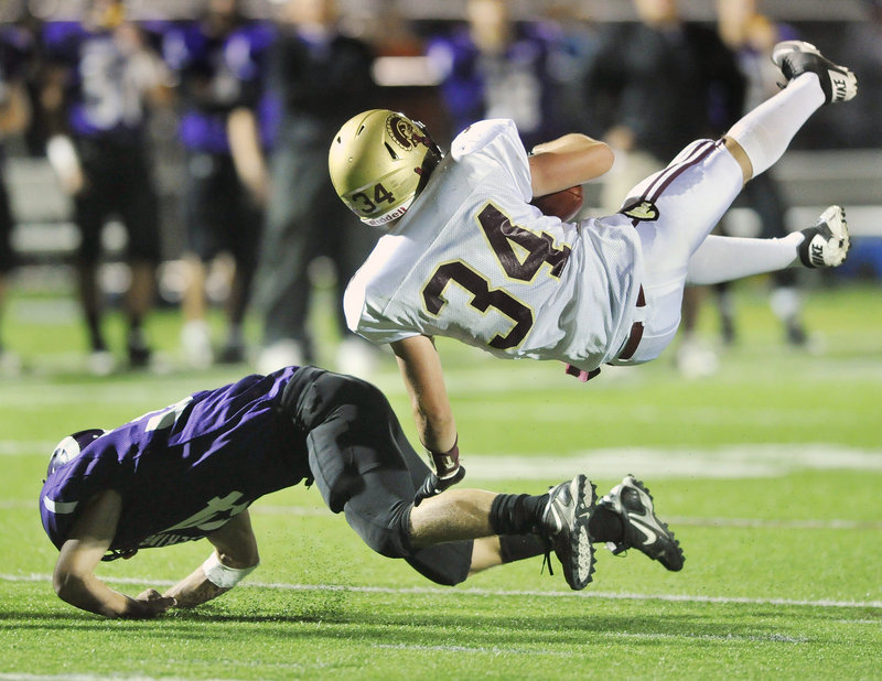 Nick Kenney, 34, who gained 107 yards rushing on 18 carries for Thornton Academy, heads to the ground Friday night after being upended by Kenny Sweet of Deering during Thornton's 28-21 victory at Memorial Field.