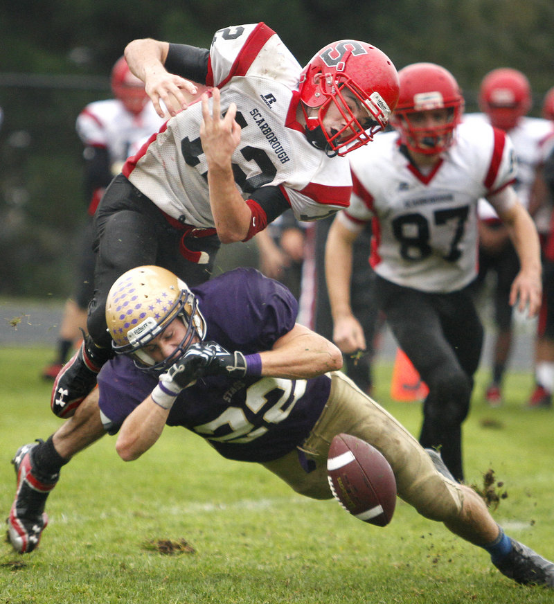 Donald Goodrich of Cheverus puts a hit on Scarborough quarterback Dillon Russo, causing a second-half fumble Saturday during the unbeaten Stags' 38-0 victory.