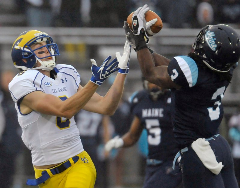 Trevor Coston of the University of Maine, right, intercepts a pass intended for Delaware's Mark Schenauer in the first quarter of a Colonial Athletic Association football game Saturday at Orono. The Black Bears had four interceptions on the way to a 31-17 victory.