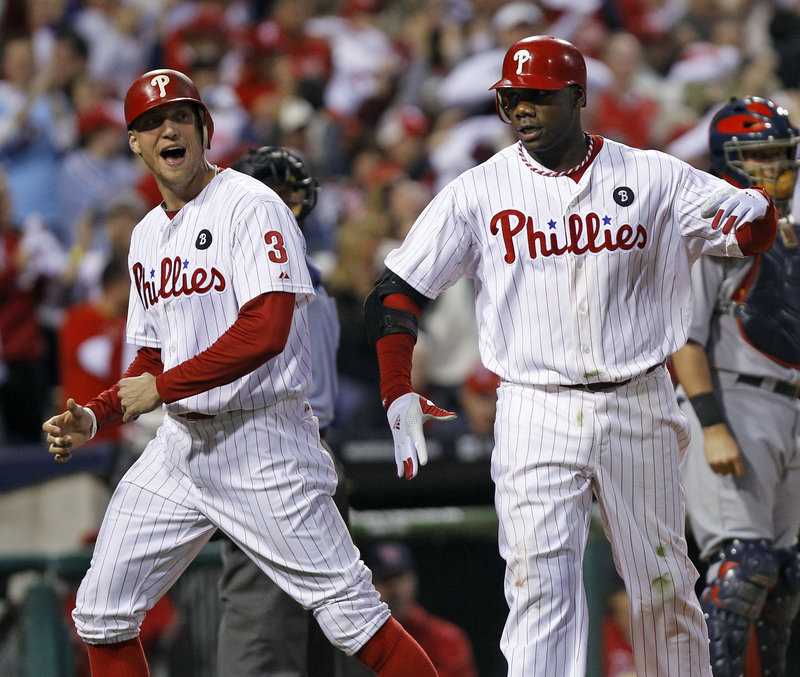 Ryan Howard, right, and Hunter Pence celebrate after Howard's three-run homer that gave the Phillies a 4-3 lead in the sixth inning on the way to an 11-6 win over the Cardinals.