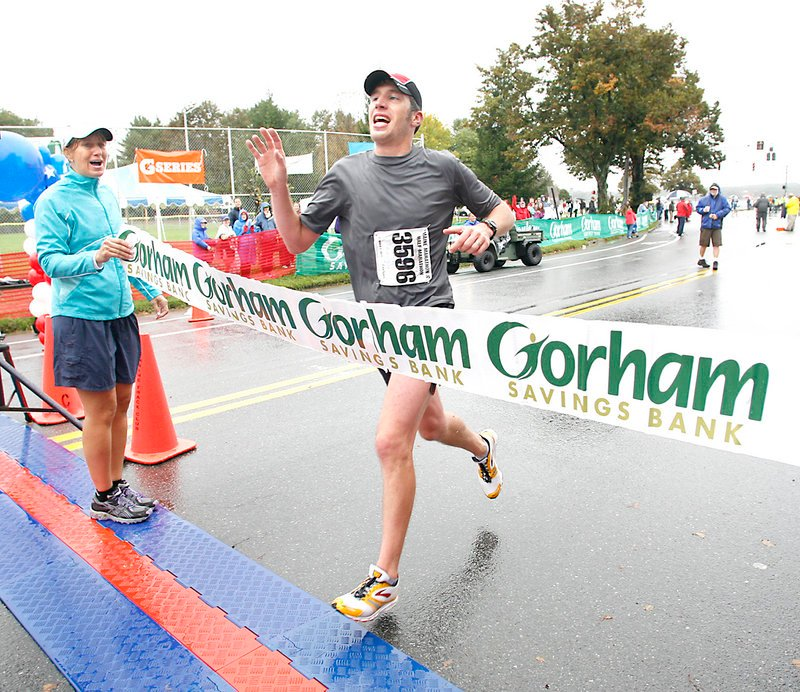 Maine Marathon winner Evan Graves of Caribou waves to supporters as he crosses the finish line Sunday. Graves ran the race in 2 hours, 36 minutes and 53 seconds. Waiting beyond the finish line were his wife and their daughter, Emma, who was born in June.