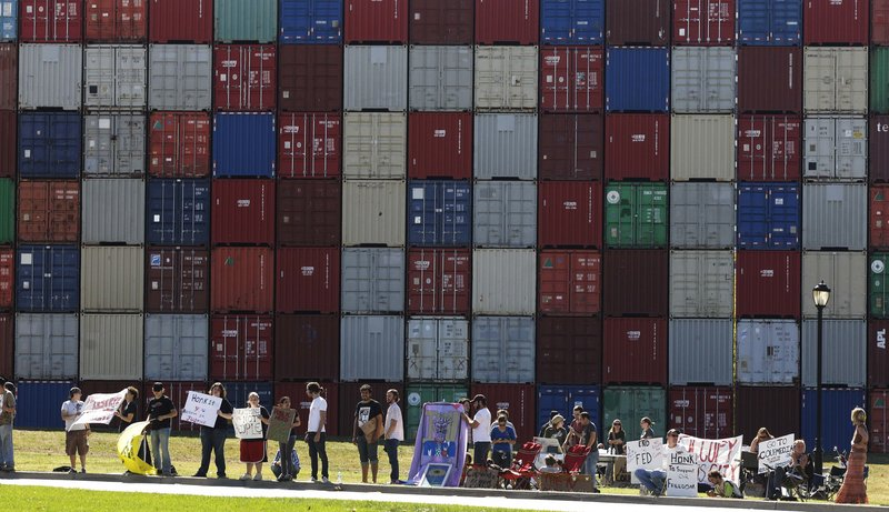 "Demonstrators stand in front of the letters ""IOU"" spelled out on shipping containers across the street from the Federal Reserve Bank of Kansas City in Kansas City, Mo., on Friday."