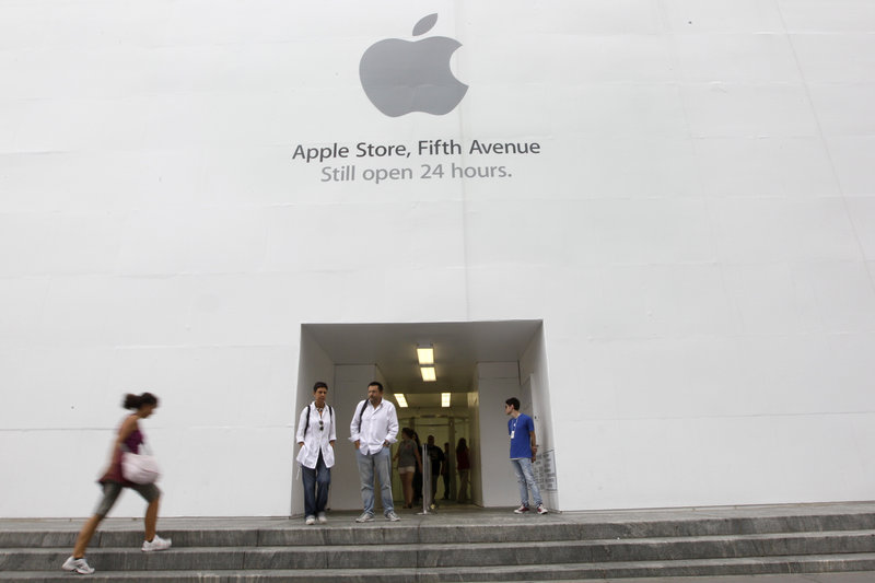 Customers stand outside the Apple flagship store on Fifth Avenue in New York. The computer and gadget maker is expected to announce a newer, more powerful version of its wildly popular smartphone today.