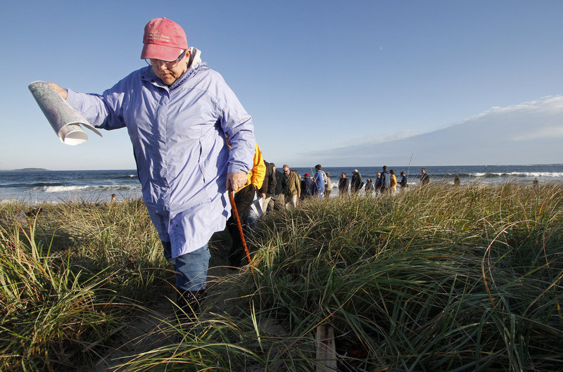 Kerry Corthell, a Scarborough Planning Board member, walks up a path from the beach with others who toured the proposed Black Point Park at Scarborough Beach on Monday. The board will hold at least one more public hearing on the proposal.