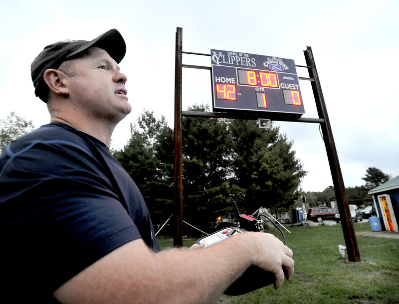John Beatty, an assistant with the Frank Harrison Middle School football team, turns on a new scoreboard at Winslow Field during an unveiling ceremony Monday in Yarmouth. The scoreboard was donated by Casco Bay Ford and was erected by local residents, welded by a local tradesman and wired by a local electrician in a community effort to improve the field through donated work. The unveiling party Monday was to thank the community for its efforts in putting up the new scoreboard at the field, which is home to both high school and middle school teams.