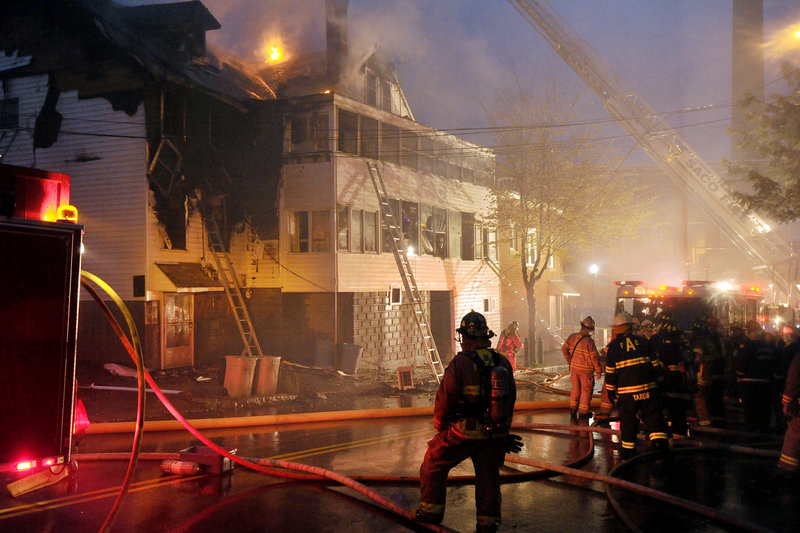 Firefighters battle a fatal fire Tuesday in an apartment building at 29 Main St. in Biddeford. Two firefighters were hospitalized after the blaze, which displaced nine residents and destroyed all of their belongings.