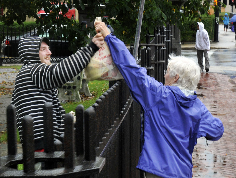 Constance Bloomfield hands bags of food over the fence at Lincoln Park in Portland to Chris Levesque, 22, of Biddeford, on Tuesday. Levesque is part of the group OccupyMaine, which had permission to set up tents in the park as part of its protest against Wall Street greed.