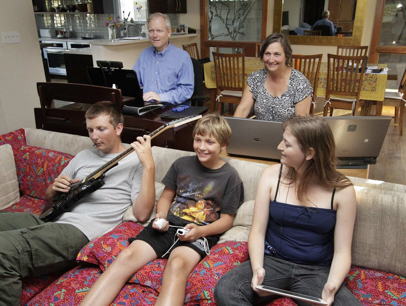 The Hartman family, parents Eric and Nia, rear, and their children, from left, sons Spencer, 16 and Evan, 11, and daughter Emily, 18, use digital devices that track their whereabouts, preferences and habits – a trend that concerns privacy advocates.