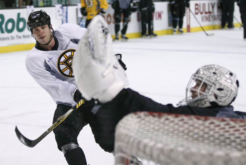 Goalie Tim Thomas makes a save on a shot by Nathan Horton at the Bruins' final practice before today's season opener.
