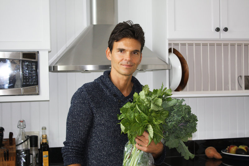 Holding fresh greens from Chase's Daily, celebrity chef Matthew Kenney, who grew up in Searsmont, pauses for a photo in the kitchen of his Belfast home.
