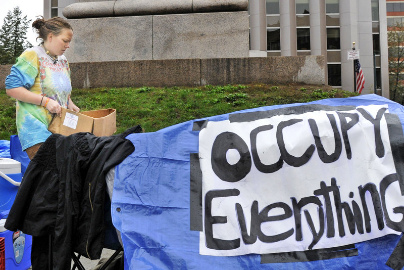 A protester in Monument Square takes down a tent Tuesday after police demanded its removal.