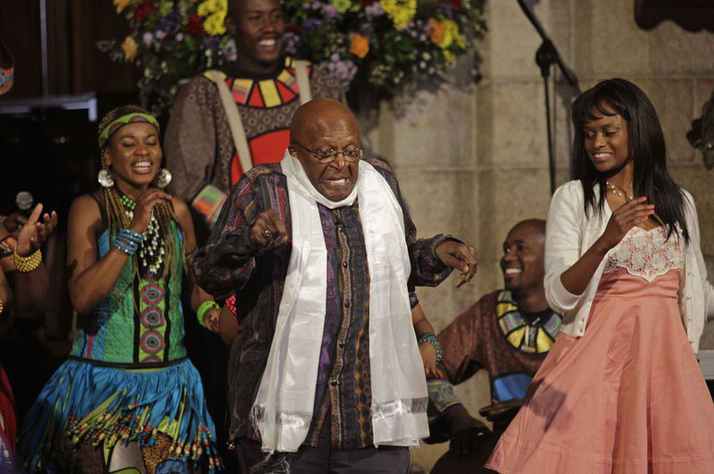 """South African Archbishop Desmond Tutu, center, dances on stage inside a church during his book launch in Cape Town, South Africa, on Thursday. Tutu is celebrating his 80th birthday with a new book of photographs, tributes and biography, """"Tutu: The Authorized Portrait."""" On Friday, public celebrations were held at St. George's Cathedral in Cape Town."""