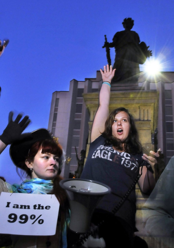 Holly Seeliger, left, and Rose Buckmore, both of Portland, raise their hands during an Occupy Maine assembly in Monument Square on Friday.