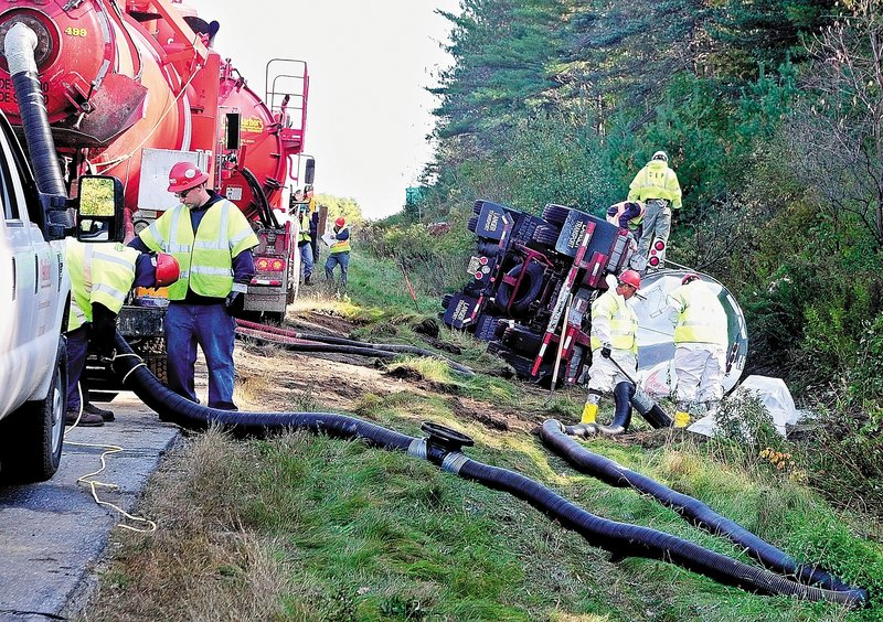 Workers pump liquid from a tanker truck that crashed on the northbound side of Interstate 95 early Friday in Augusta. Northbound traffic backed up for miles as the highway was reduced to one lane while crews continued the cleanup.