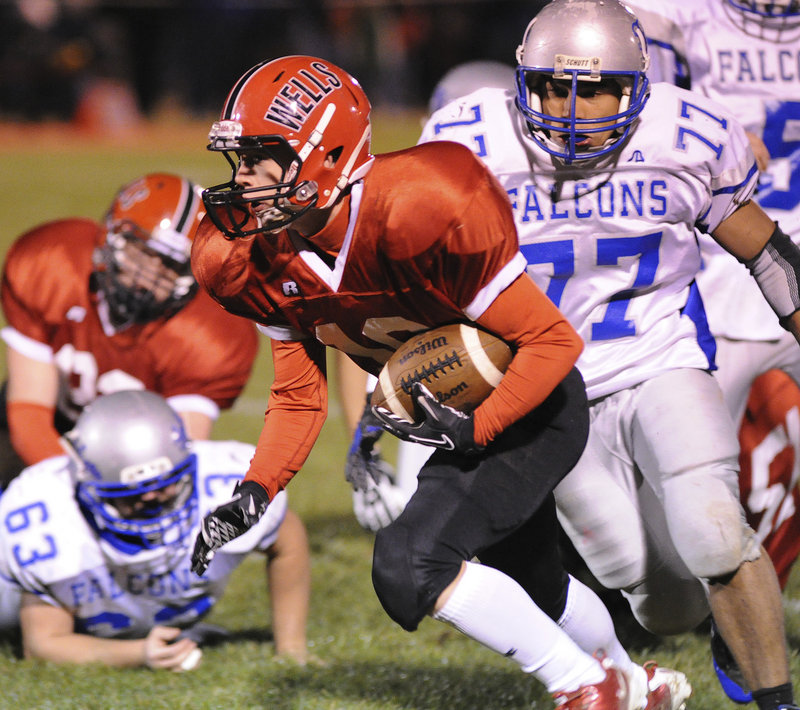 Dylan Stevens of Wells looks for more yardage Friday night after slipping past Santos Rodriguez of Mountain Valley during their Western Class B showdown. Wells ended Mountain Valley's 17-game winning streak with a 28-12 victory.
