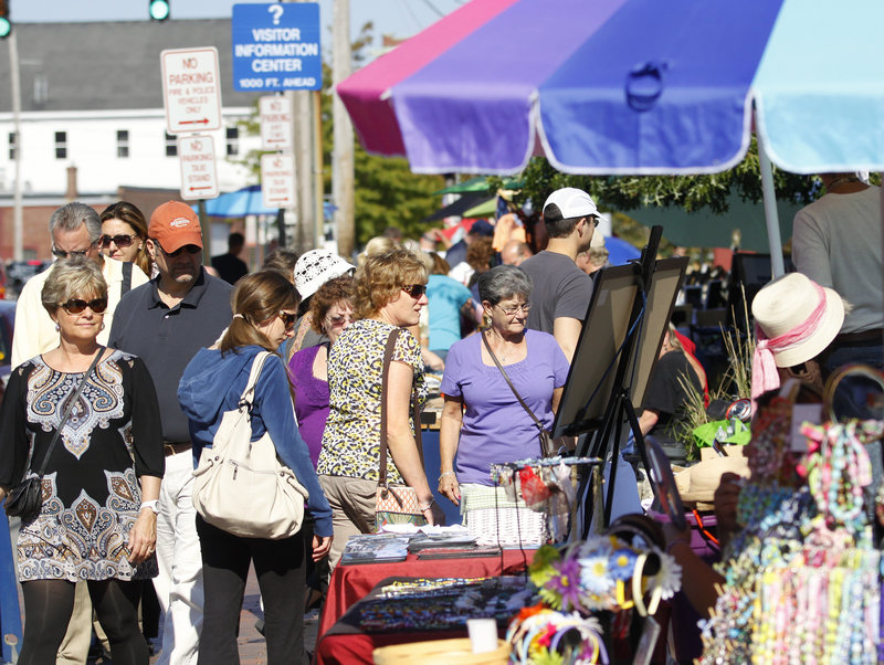 Shoppers browse the artisans' booths at Bell Buoy Park near the ferry terminal in Portland on Saturday, as 2,250 passengers from a visiting cruise ship converged on the city. The vendors create a lively atmosphere for cruise arrivals.