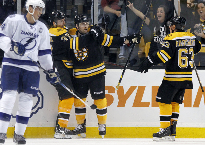 Rich Peverley of the Bruins, center, celebrates his goal with teammates Patrice Bergeron, left, and Brad Marchand as Vincent Lecavalier of the Lightning skates by in the third period.