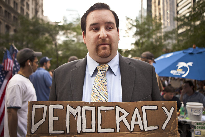 """A man who asked to be identified only as """"Dustin"""" holds a sign during the Occupy Wall Street protest in New York on Monday. The protest over class and wealth is entering its fourth week."""