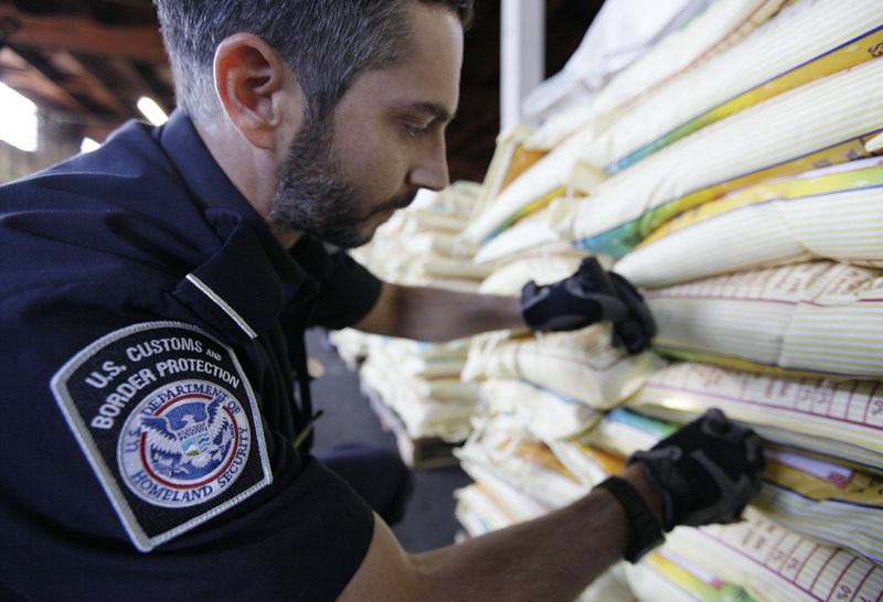 Mark Murphy, of U.S. Customs and Border Protection, examines bags of rice. Pest invasions have consequences such as higher grocery prices and substandard produce.
