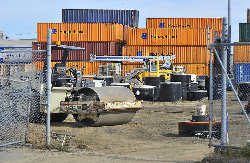 The pavement in a parking lot at the marine terminal has been removed as workers prepare to reinforce the surface so the lot can be used as additional storage for cargo containers.