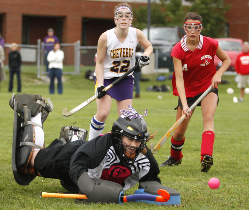 Cheverus goalkeeper Libby DesRuisseaux makes a diving save in the first half Wednesday as Sarah LaQuerre of the Stags, left, and Natalie Ledue of Sanford look on. Sanford came away with a 3-2 victory in overtime.
