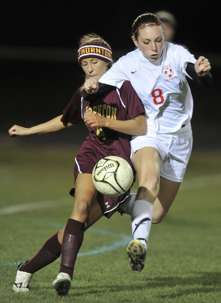 Jamie Durie of Thornton Academy, left, attempts to control the ball and hold off Clara Ellis of South Portland.