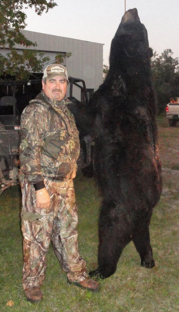Tony Weber of North Dakota is dwarfed by the 7-foot bear he shot in September.