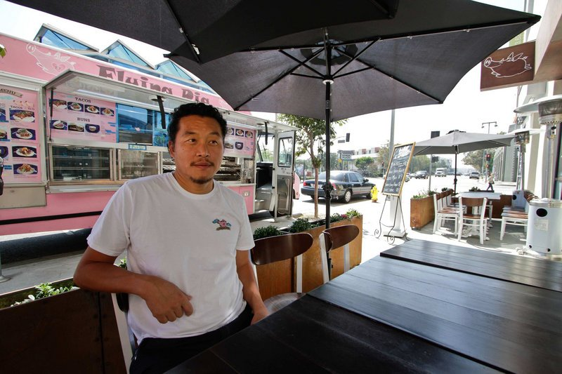 Owner Joe Kim sits at an outdoor table at the newly opened Flying Pig restaurant in Los Angeles, Calif. The Flying Pig started out as a food truck, visible at the rear, as a way for Kim to test out recipes before launching a restaurant.