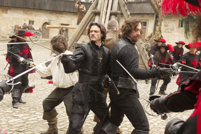 "Logan Lerman (white shirt), Luke Evans, Ray Stevenson (back to camera) and Matthew Macfadyen circle the wagons in ""The Three Musketeers."""